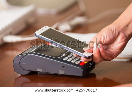 Easy and fast way to pay the shopping accounts, mobile phone near a credit card machine, hand holding mobile phone