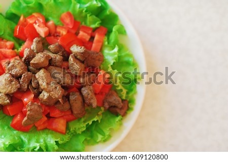 Easy diet salad with cherry tomatoes chicken liver and lettuce on a white plate background, top view space for text.