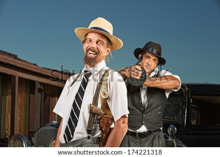 Easygoing vintage mobster with guard aiming gun - stock photo