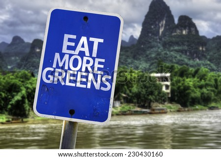 Eat More Greens sign with a forest background - stock photo