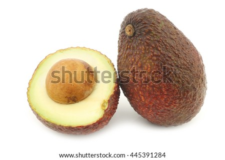 Eat ripe avocado and a cut one on a white background - stock photo