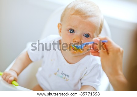 Eat smeared pretty baby girl eating from spoon - stock photo