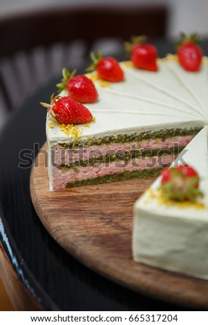 Eat tasty cake with pistacchio & strawberry biscuit decorated with fresh straberries on top.Creamy pie with sweet good taste.Pastry product in Italian restaurant menu for desserts