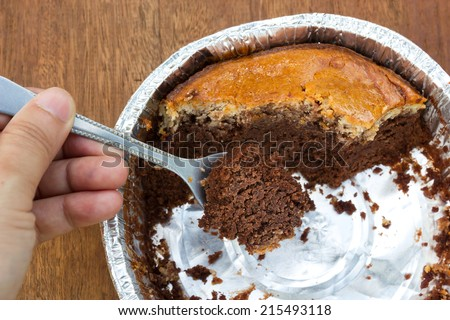 Eaten - brownie Cheese Cake in aluminium foil cup. Select focus on a cake in spoon.
