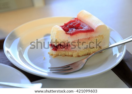 Eaten Strawberry Cake on white plate with one fork