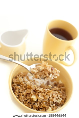 Eating a bowl of healthy muesli for breakfast with a mouthful raised on a spoon and a mug of coffee in the background - stock photo