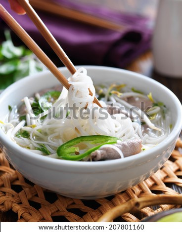 eating a bowl of pho with chopsticks - stock photo