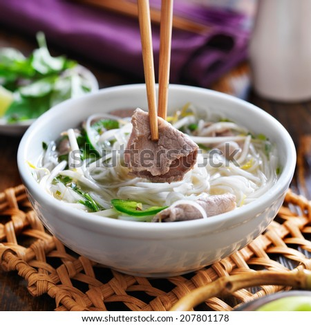eating a bowl of pho with chopsticks and picking up beef - stock photo