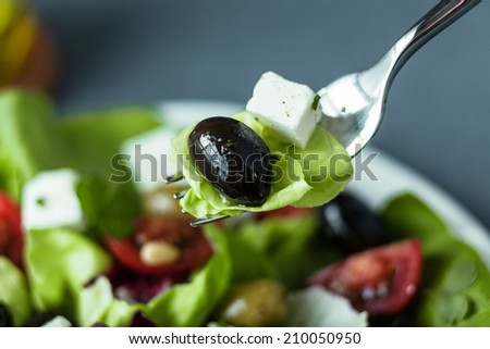 Eating a mixed Greek salad with a black olive, feta cheese and lettuce on a fork above a plate of salad with focus to the fork - stock photo