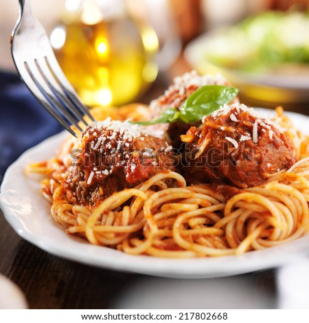 eating a plate of spaghetti and meatballs with fork - stock photo