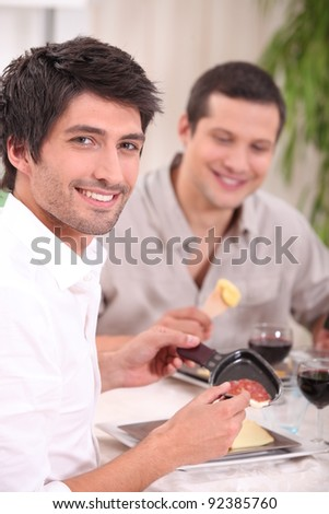 Eating a raclette. - stock photo