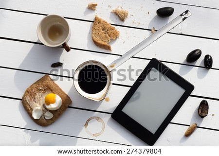 Eating and E-Reading. Buttered Toast with a Boiled Egg, Olives and Black Coffee - stock photo