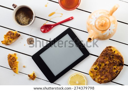 Eating and E-Reading. Egg and Cheese Sandwiches with Lemon and Honey Chamomile Tea - stock photo