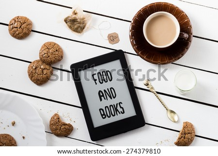 Eating and E-Reading. Flourless Walnut Cookies and Black Tea with Milk. FOOD AND BOOKS Text Included - stock photo