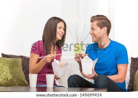 Eating Asian food. Beautiful couple eating Asian food from food containers and smiling - stock photo