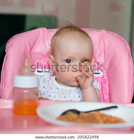 eating baby with finger in mouth - stock photo