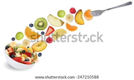 Eating flying fruit salad with fork, fruits like apples, oranges, kiwi, peach, banana and strawberry - stock photo