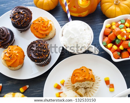 Eating Halloween cupcakes with orange and black icing. - stock photo
