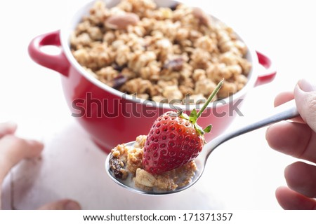 Eating healthy breakfast with milk,muesli and strawberry.