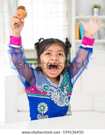 Eating ice cream. Cheerful Indian Asian girl enjoying an ice cream. Beautiful child model at home. - stock photo