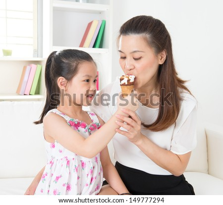 Eating ice-cream. Happy Asian family eating ice-cream at home. Beautiful child feeding mother. - stock photo