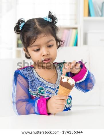 Eating ice cream. Indian Asian girl enjoying an ice cream at home. - stock photo