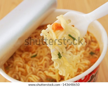 Eating Instant Noodles with a Plastic Fork - stock photo