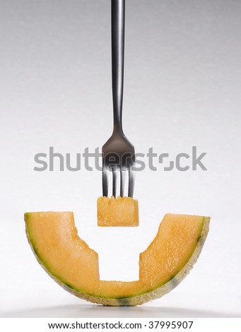 Eating melon. fork puncturing melon piece.