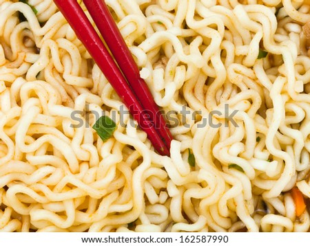 eating of cooked instant ramen by red chopsticks close up