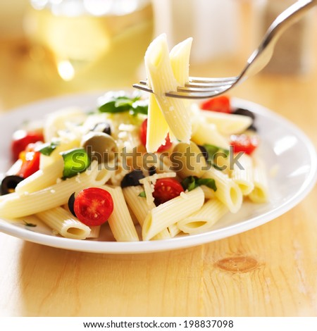 eating penne pasta salad with fork - stock photo
