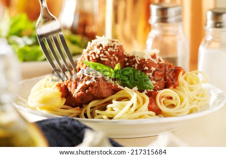 eating spaghetti and meatballs with fork - stock photo