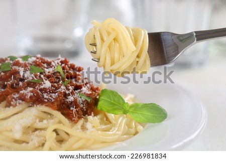Eating spaghetti Bolognese or Bolognaise noodles pasta meal with fork - stock photo