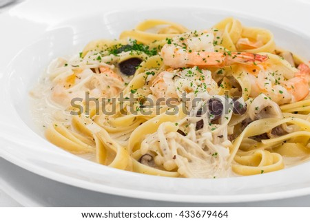 Eating Spaghetti Carbonara with Aluminum Fork and Knife in a White Ceramic Dish in a Restaurant