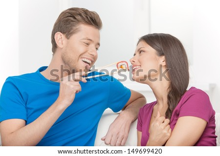 Eating sushi together. Beautiful couple eating sushi while sitting close to each other on the couch - stock photo