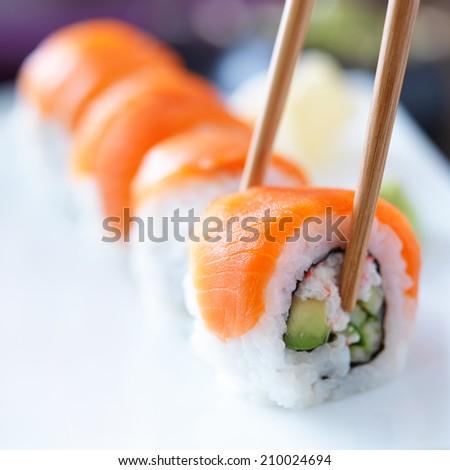 eating sushi with chopsticks - stock photo