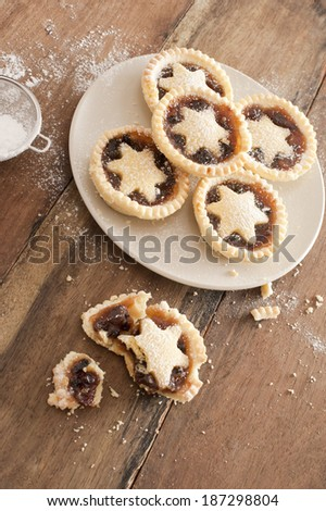 Eating tasty home baked Christmas mince pies freshly baked in a rustic kitchen and decorated with pastry stars - stock photo