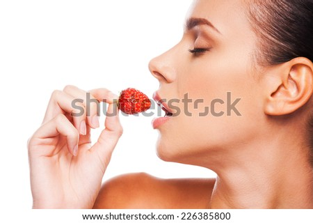 Eating with passion. Side view of beautiful young shirtless woman holding strawberry in her hand and keeping eyes closed while standing against white background - stock photo