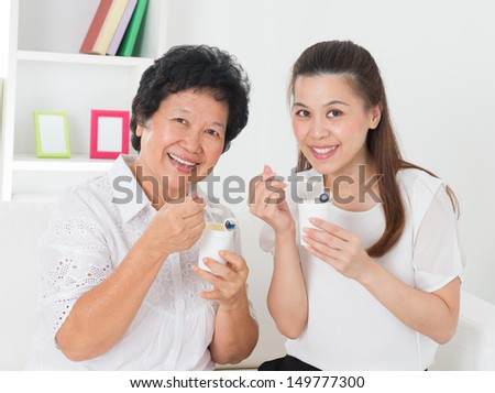 Eating yogurt. Happy Asian family eating yoghurt at home. Beautiful senior mother and adult daughter, healthcare concept. - stock photo
