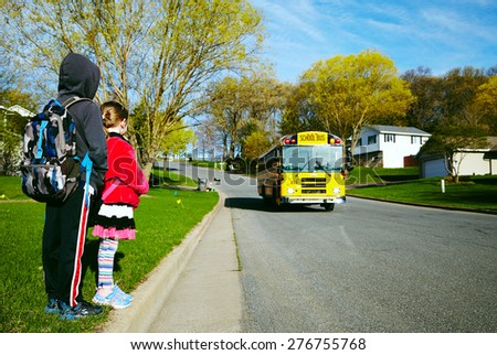 EAU CLAIRE, USA â?? April 29, 2015. Young girl and boy waiting the schoolbus