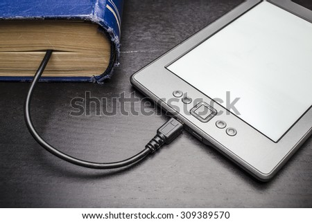eBook connected to the old thick blue book with a cable, and download information from there - stock photo