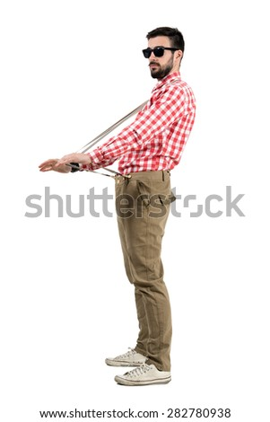 Eccentric hipster stretching suspenders looking at distance.  Full body length portrait isolated over white background.  - stock photo