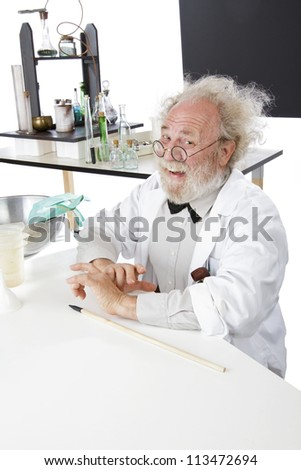 Eccentric smiling senior scientist in his lab with blackboard and pointer. - stock photo