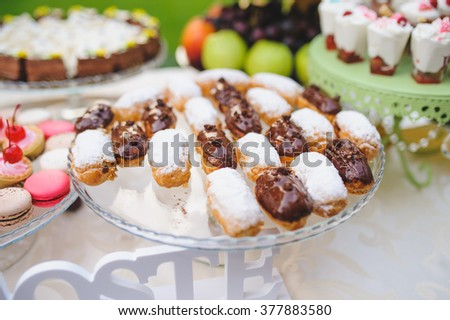 eclairs with chocolate and powdered sugar on glass tray