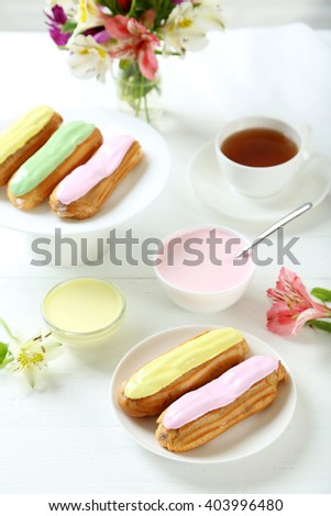 Eclairs with glaze on a white wooden table