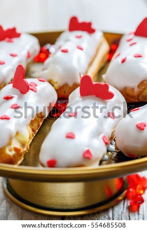 Eclairs with the decor of red hearts on a bronze stand close up, selective focus.
