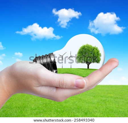 Eco bulb with wind turbines and tree in hand. Green energy concept.