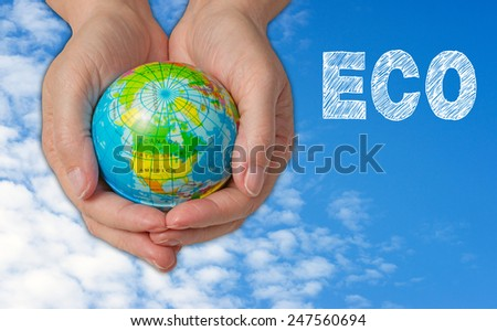 ECO - Ecology - earth with female hands and blue sky with some clouds in the background - stock photo