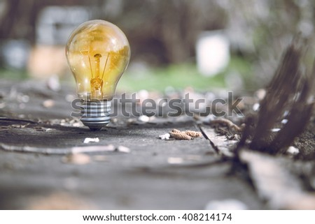 Eco Friendly Energy - light bulb glowing in the grass - stock photo