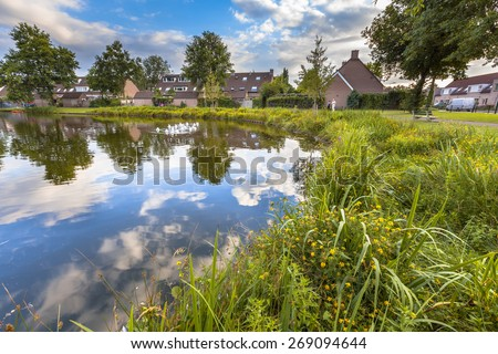Eco friendly lakeside with gentle slope to stimulate growth of wildflowers and swamp vegetation in a recreational park in Soest, Netherlands - stock photo