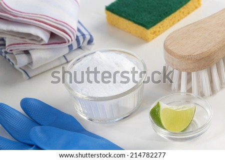 Eco-friendly natural cleaners Vinegar, baking soda, salt, lemon and cloth on wooden table Homemade green cleaning